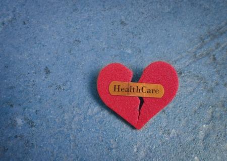 Gebroken rood hart met een pleister en Healthcare tekst, op blauw Stockfoto