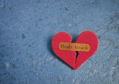 the attack: Broken red heart with a bandaid and Heart Attack text Stock Photo