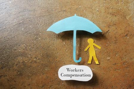 trabajadores: Hombre de papel bajo un paraguas con la nota de Compensaci�n de Trabajadores debajo - en el concepto de lesi�n en el trabajo