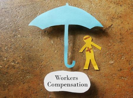 trabajadores: hombre de papel vendada bajo el paraguas con la nota de Compensaci�n de Trabajadores de abajo