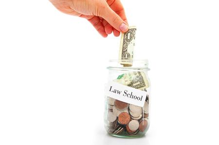 college fund savings: hand putting a dollar into a Law School coin jar Stock Photo