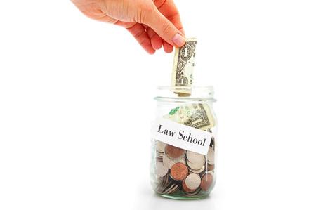 law school: hand putting a dollar into a Law School coin jar Stock Photo