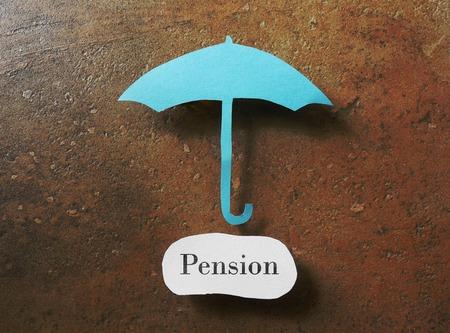 nestegg: Paper umbrella over a pension message Stock Photo