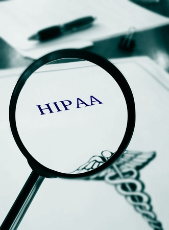 government regulations: HIPAA document with magnifying glass Stock Photo