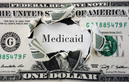 medicaid: Hole torn in a dollar bill with medicaid text Stock Photo