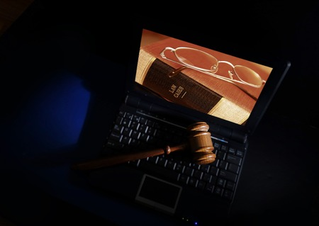 lawsuit: Judges court gavel on a laptop with law books image on the screen