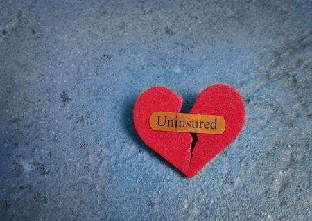 bandaid: Broken red heart with a bandaid and Uninsured text -- lack of health insurance concept Stock Photo