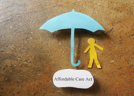 affordable: Paper person under an  Affordable Care Act concept umbrella - Obamacare concept