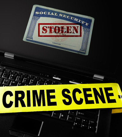 stolen identity: Social Security card with Stolen stamp on a laptop with crime scene tape -- Identity Theft concept