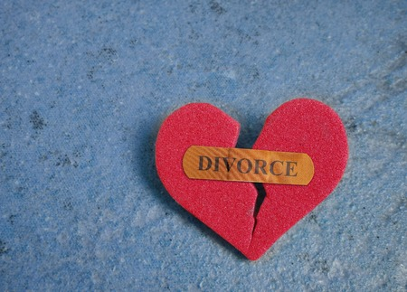 marriage counseling: Broken red heart with a Divorce bandaid, on blue