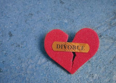 divorcio: Corazón rojo quebrado con una tirita Divorcio, en azul Foto de archivo