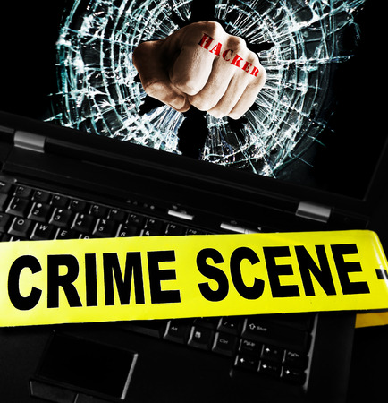 crime: Hacker fist on laptop screen with crime scene tape Stock Photo