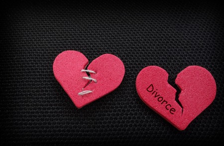 Two broken hearts, one with threaded stitches, one with Divorce message