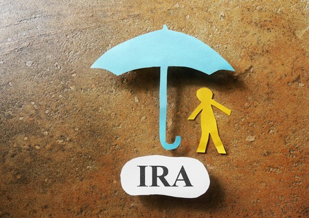 Paper cutout figure with an umbrella and IRA message - Individual Retirement Account concept