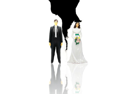 plactic: plactic wedding couple figures on ripped paper - (divorce concept) Stock Photo