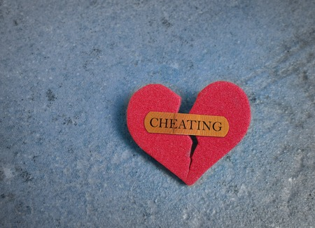 Broken red heart with a bandaid and Cheating text, on blue