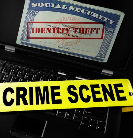 seguridad social: Tarjeta de Seguro Social con el sello de robo de identidad en la pantalla del portátil con cinta policial Foto de archivo