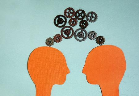 sameness: Two paper heads with metal gears - teamwork or sameness concept