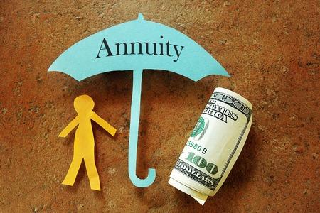 Annuity Regenschirm über einem Papier Ausschnitt Person und hundert Dollar Bill Standard-Bild - 44483912