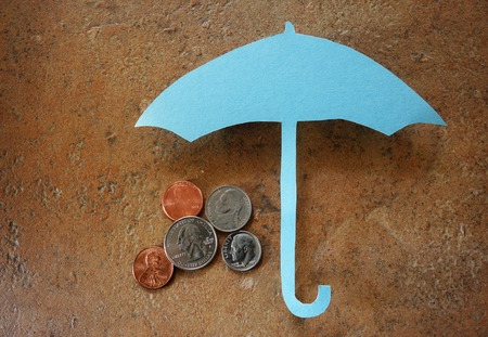 financial protection: Coins under paper umbrella -- financial security or savings concept