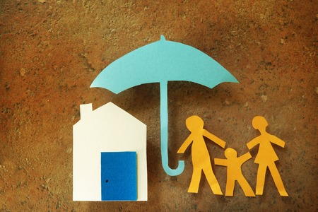 life insurance: Paper cutout family with house under an umbrella