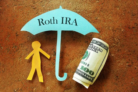 Paper cutout person under a Roth IRA umbrella Stock Photo