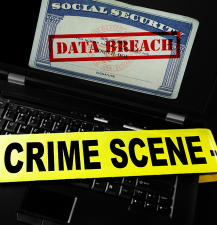data theft: Data Breach text on Social Security card with crime scene tape on laptop computer