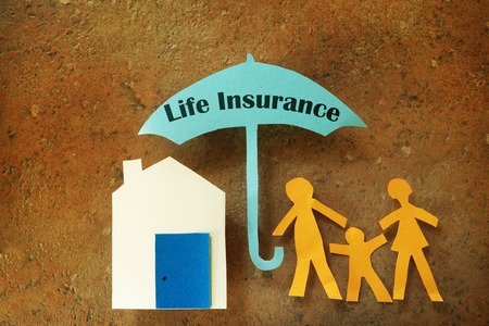 Paper cutout family with house under a Life Insurance umbrella Stockfoto