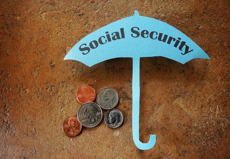 seguridad social: Monedas bajo el paraguas de papel con el texto de la Seguridad Social Foto de archivo