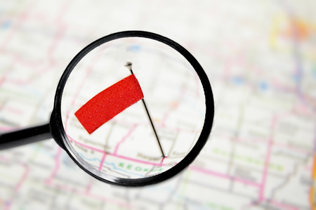 specific: locator pin flag in a map with magnifying glass Stock Photo