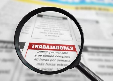 lupa: Sección Empleo de un periódico en español con lupa Foto de archivo