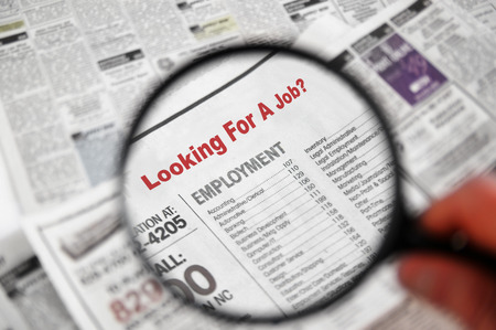 paper work: Magnifying glass over Jobs section of newspaper classifieds Stock Photo