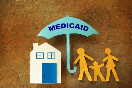 medicaid: Paper cutout family with house under a Medicaid umbrella
