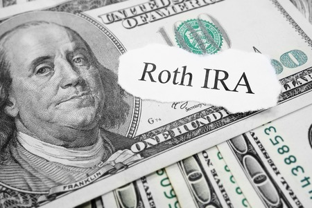 Roth IRA paper message on hundred dollar bills Stock Photo