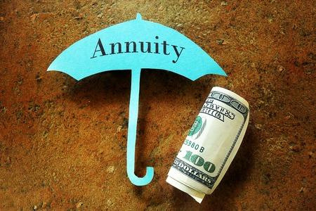 annuities: Hundred dollar bill under a paper umbrella with Annuity text Stock Photo