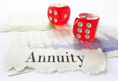 annuities: Annuity newspaper headline on stock market charts with dice