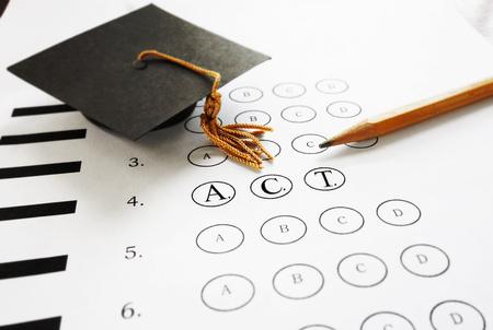 ACT college entrance test with pencil and  graduation cap Foto de archivo
