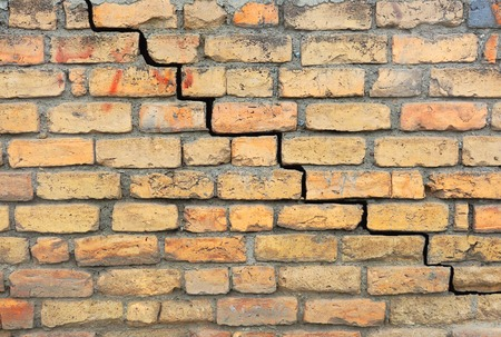 earthquake crack: Brick foundation with a crack in the mortar