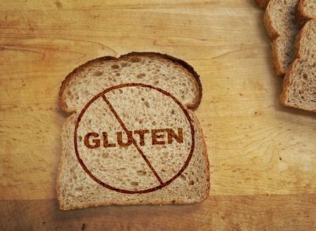 Slice of wheat bread with Gluten text crossed out -- Gluten free concept