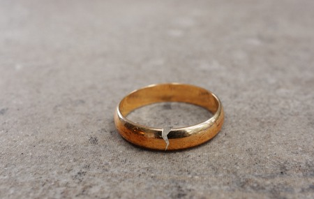 broken relationship: Gold wedding ring with a crack in it -- divorce concept