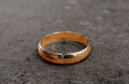 relationship breakup: Cracked gold wedding ring -- divorce concept