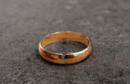 Cracked gold wedding ring -- divorce concept