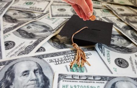 Hand geld steken in een graduation cap - student aflossing van de lening of hogeschool besparingenconcept