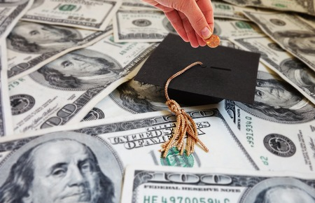 college: Hand putting money into a graduation cap -- student loan repayment or college savings concept
