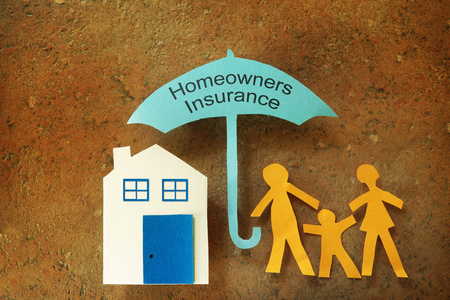 homeowners: Paper cutout family with house under a homeowners insurance umbrella