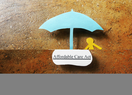 affordable: Paper person under Affordable Care Act umbrella - Obamacare concept