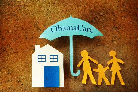 obama care: Paper cutout family with house under an Obama Care umbrella