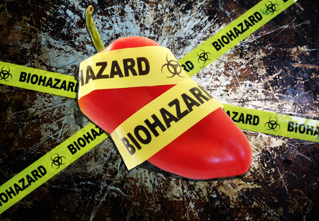 genetically modified crops: Yellow biohazard tape across a pepper -- food safety concept
