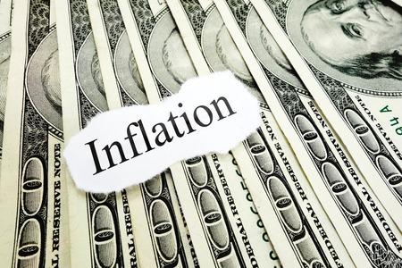headline: Inflation newspaper headline on hundred dollar bills Stock Photo