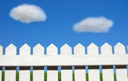白いピケット フェンス、緑の芝生と青空
